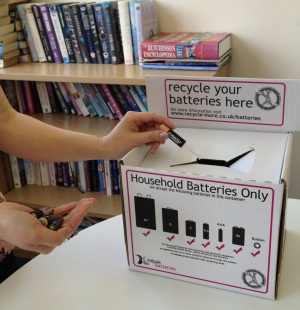 Person recycling batteries in a library
