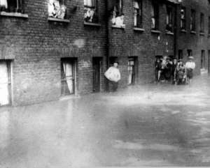 People stood outside of their flooded houses in 1914